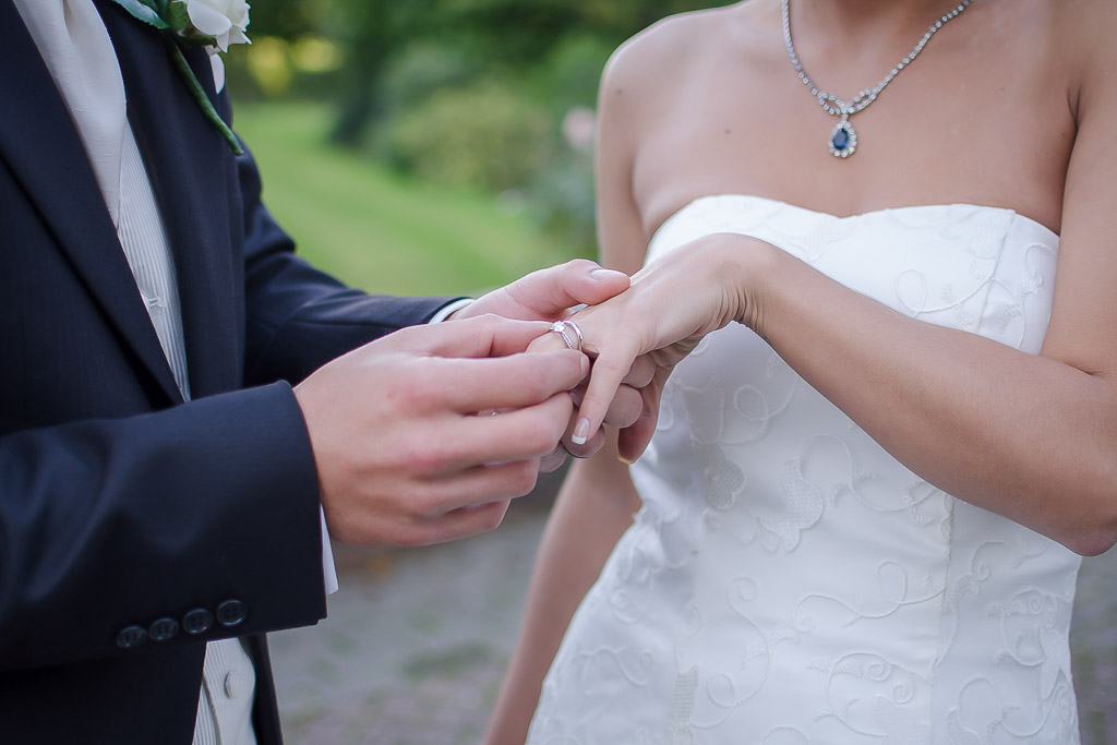 Groom placing wedding ring on brides finger at East Court