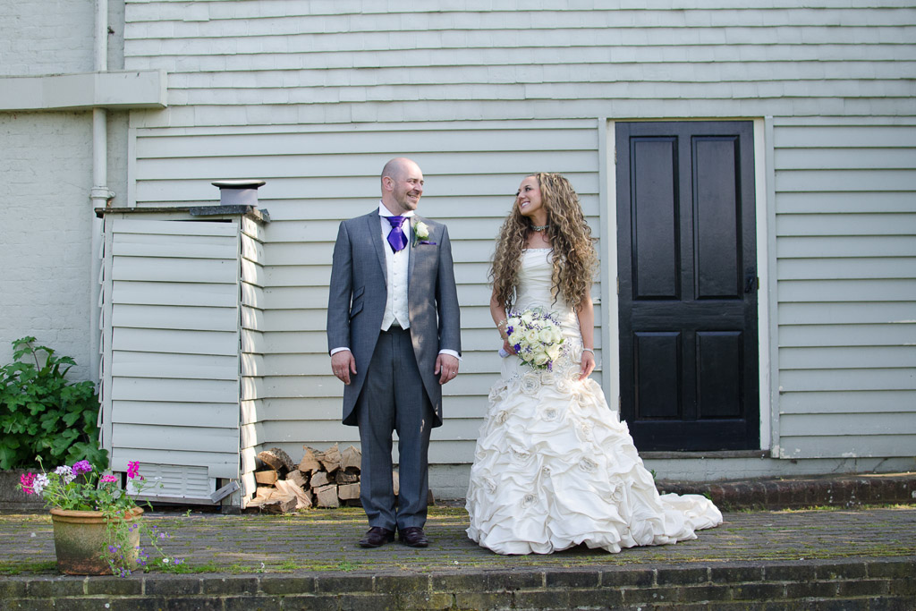 Quirky wedding photography with bride and groom looking at ecah other with top hat and other features