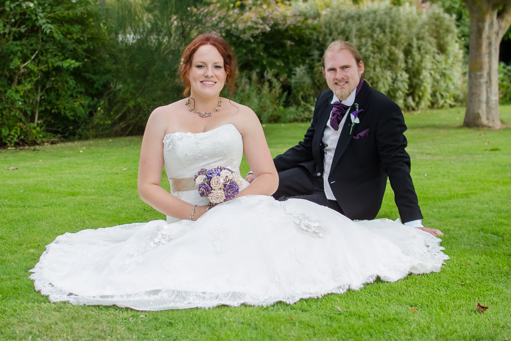 Bride sat on floor with dress fanned out and Groom behind