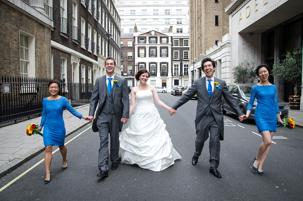 Bride, groom, bridesmaids and best man walking hand in hand down London street