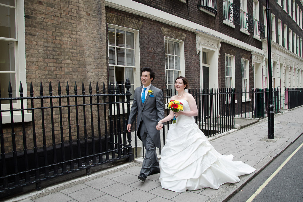 Bride and groom walking along the pavement outside wedding venue in London