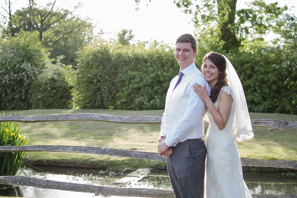 Bride and groom by the lake at Coltsford Mill