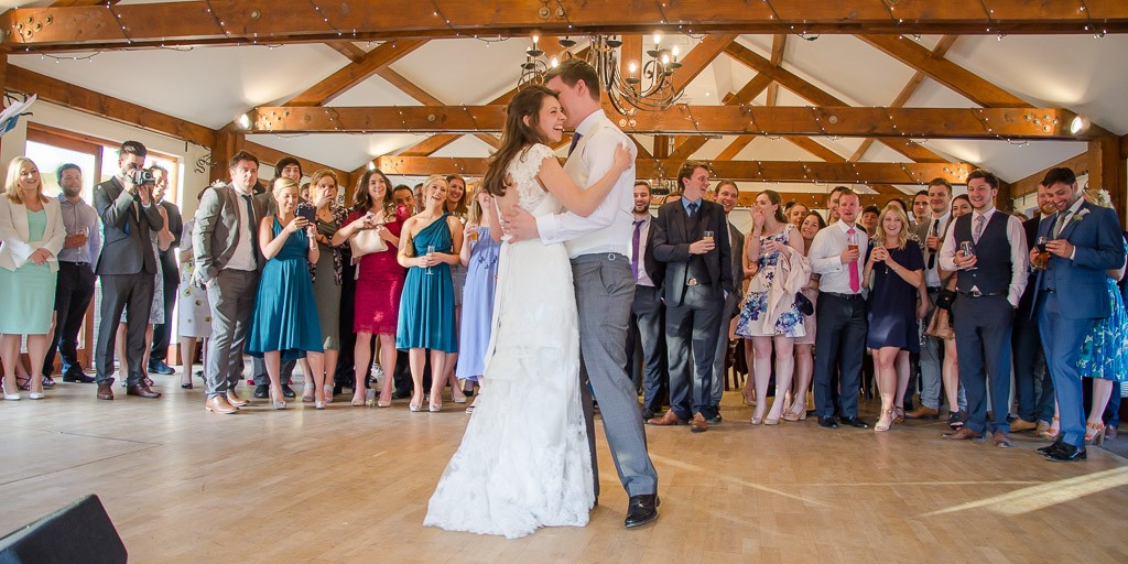 Bride and grooms first dance with friends and family watching