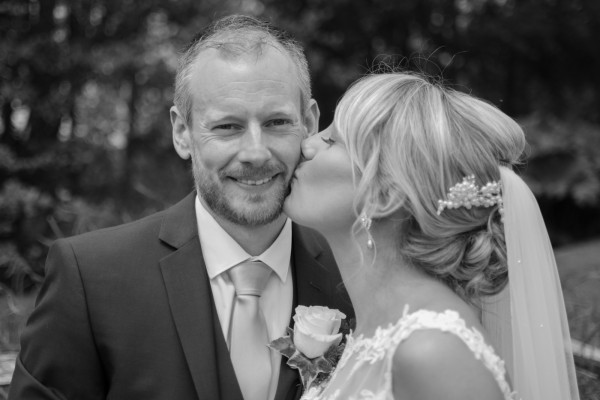 Bride kissing groom on cheek at Coltsford Mill, Oxted