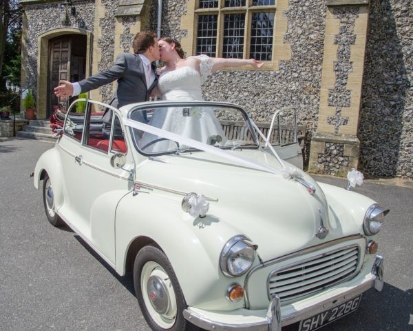 Bride and groom celebrating in vintage car at Oxted