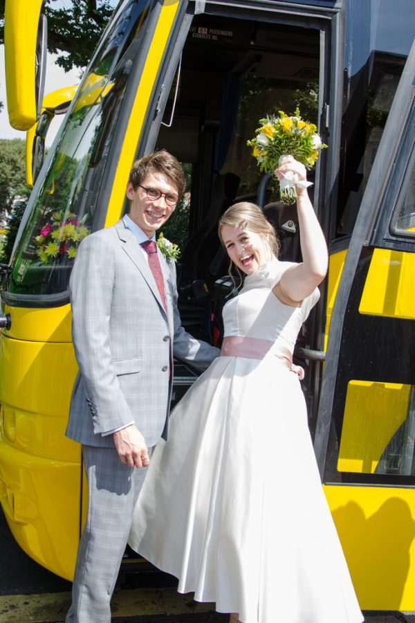Bride and groom boarding wedding bus