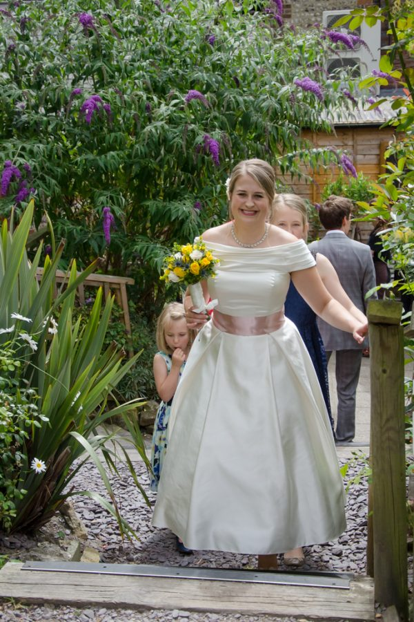 Bride in the pub garden with bouquet