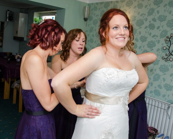 Bride and her bridesmaids getting into dress