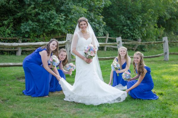 Bride with bridesmaids spreading her dress