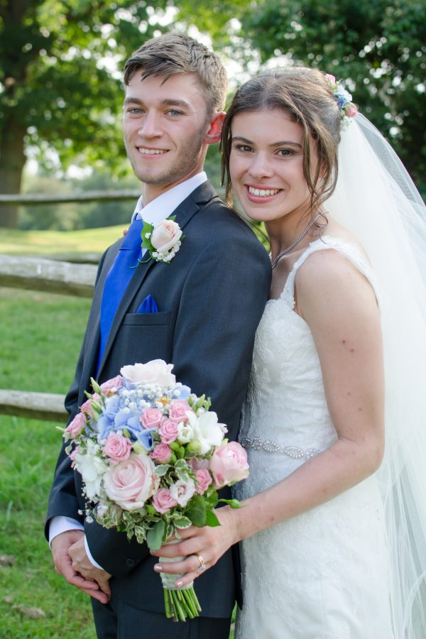 bride behind groom holding bouquet at caterham wedding